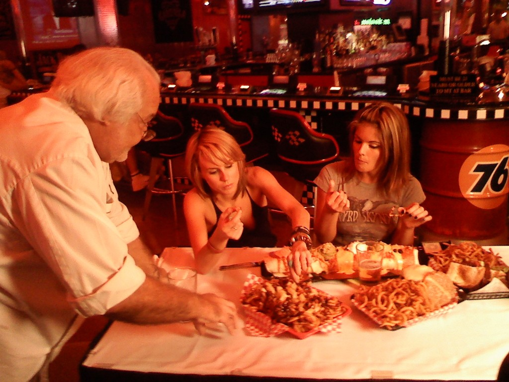 Exec Chef Tim Emert explains the finer points of pineapple chocolate curly fries to Playboy Playmate Laura Croft & Vegas Showgirl Kiltie Colleen at NASCAR Cafe/photo:ECG