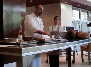 Chef Pouessel demonstrates the art of foie gras while Megan Romano observes.
